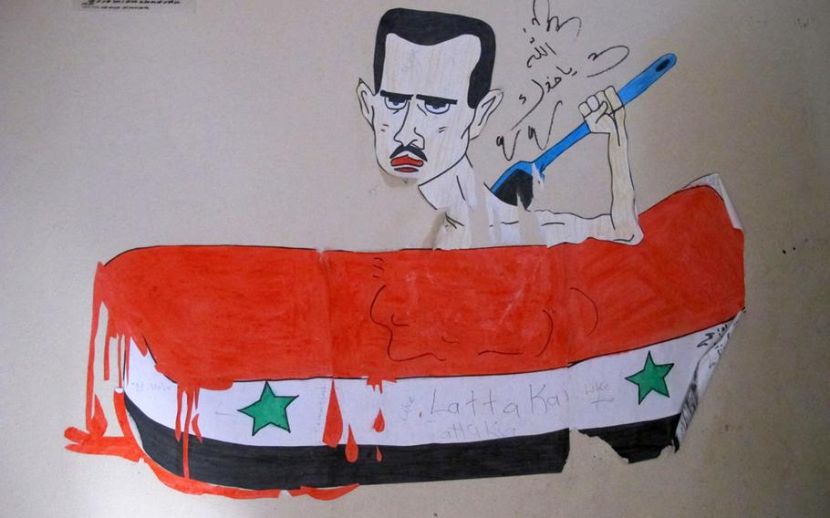 Students at the Mohamed al-Fath School for Syrian refugee children in Antakya, Turkey, express their experiences in drawings.  This one depicts Syrian President Bashar Assad bathing in the blood of the Syrian people.