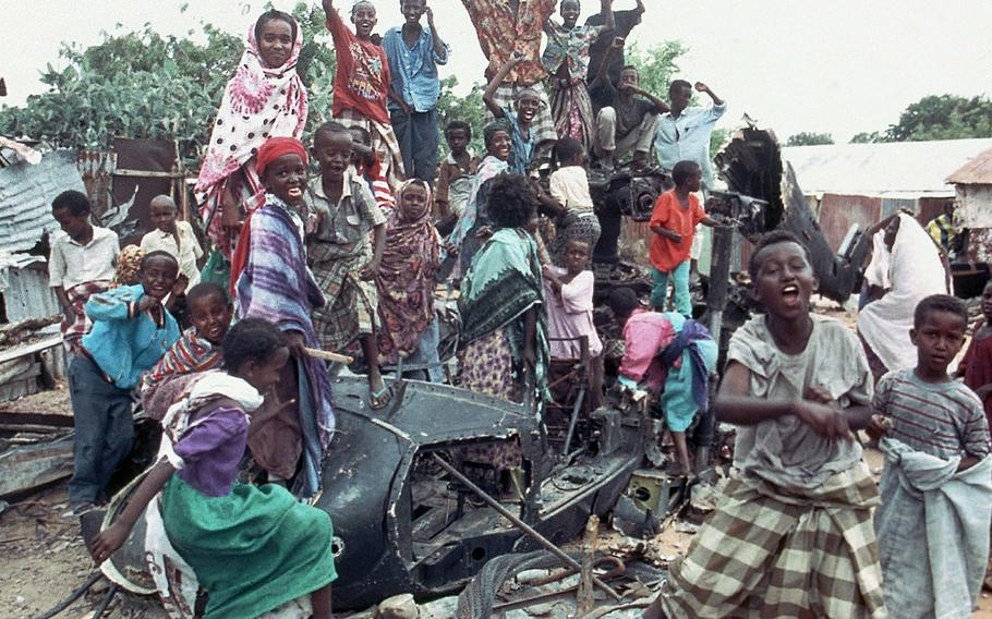 A group of young Somalis chant anti American slogans while sitting atop the burned out hulk of a U.S. Black Hawk helicopter in Mogadishu, Somalia on Oct. 19, 1993. The helicopter was one of two shot down during a firefight with Somali guerrillas in which 18 U.S. servicemen were killed along with one Malaysian peacekeeper and 300 Somalis.