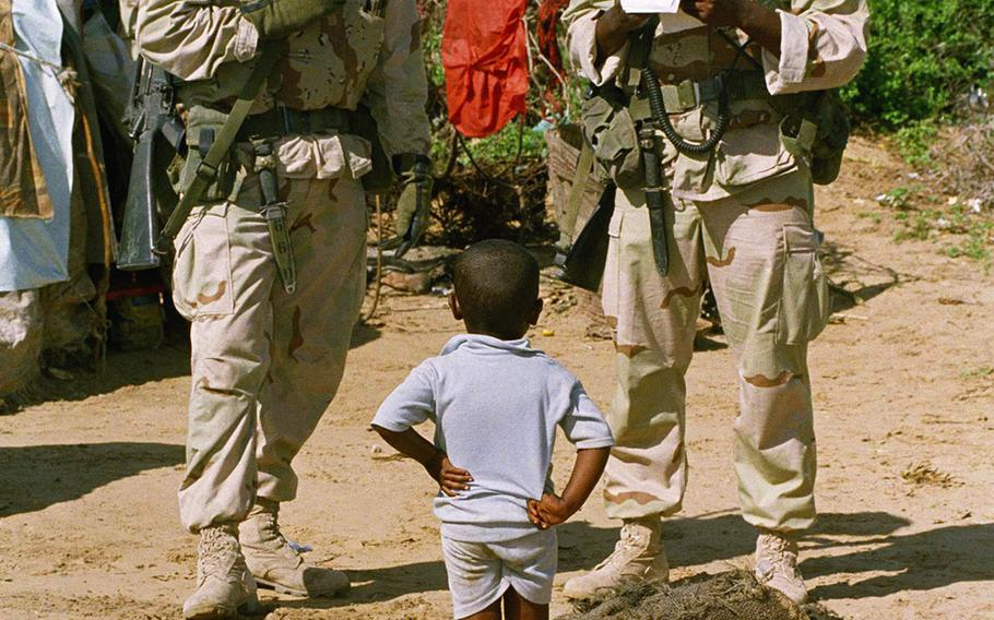 Marine Lance Cpl. Orlando Wilkins, right, of Detroit, searches through his Somali phrase book to speak to a young refugee boy as PFC David Wilson of Phoenix, Ariz, looks on at the Lafoole refugee center near Mogadishu, Tuesday, Jan. 5, 1993. Three weeks into the mission, some African-Americans hear the echoes of their origins and feel a strong bond.