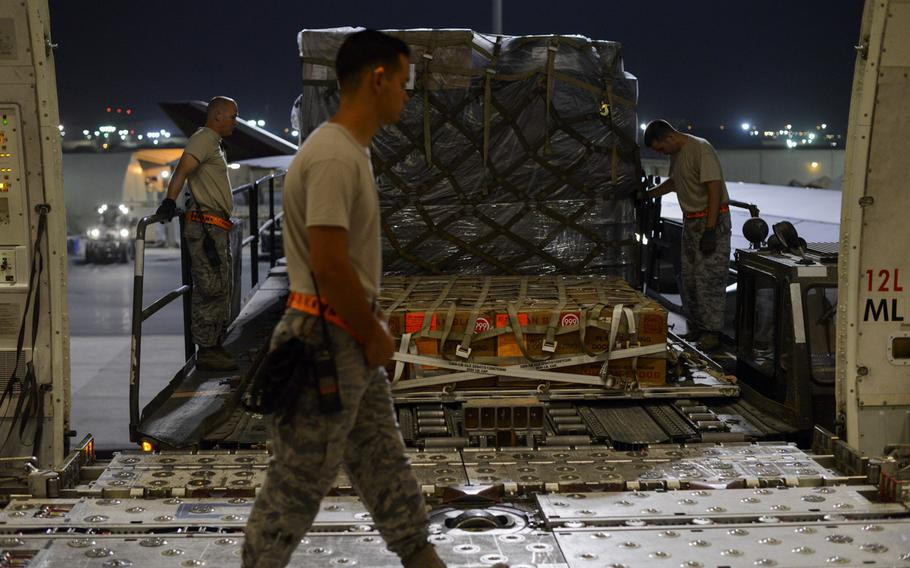 From left, Staff Sgt. Bradley Hoffstetter, Airman 1st Class Vi Matoswiscovitch and Staff Sgt. Matthew Gregg move cargo from a Boeing 747 at an Air Force base in Southwest Asia on Sept. 10, 2013. Included in the cargo was a shipment of blood headed for Afghanistan.