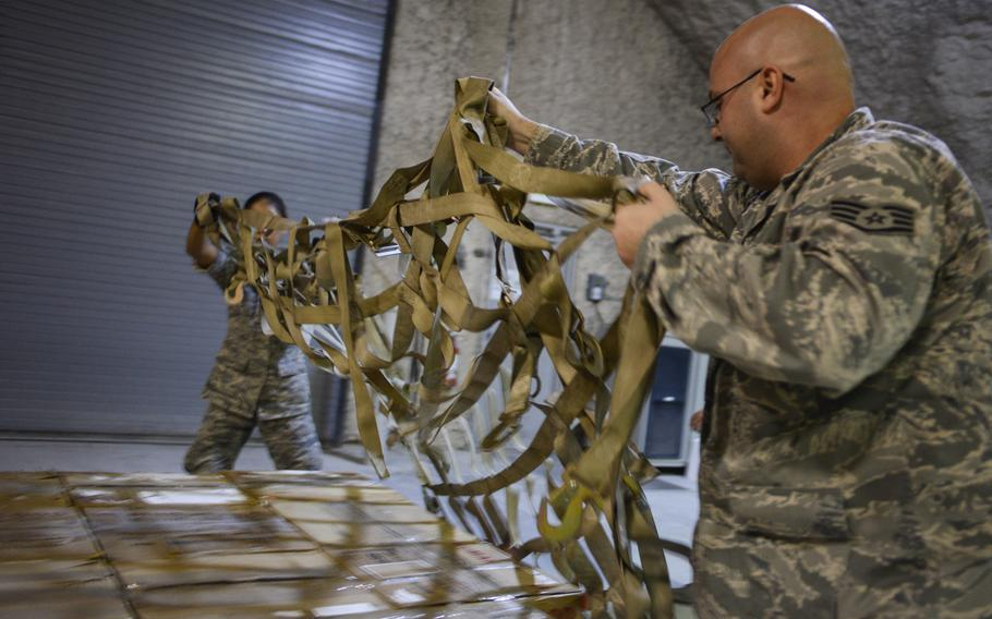Staff Sgt. Aaron Gerasch, front, and Airman 1st Class Patricia Ibanez finish building a pallet of blood for a shipment to Afghanistan on Sept. 13, 2013.