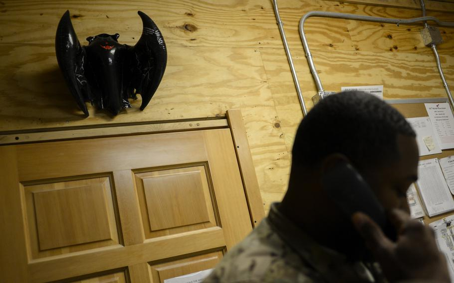 A vampire bat hangs above the door to the 932nd Blood Support Detachment's blood bank as 1st Lt. Johnny Arterson talks on the phone at Kandahar Air Field, Afghanistan, on Sept. 14, 2013.