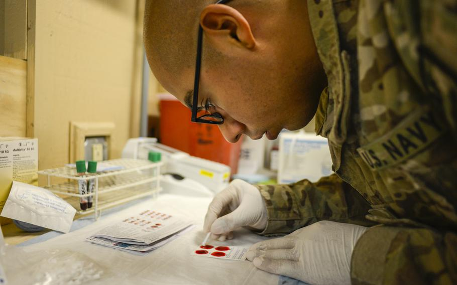 Petty Officer 2nd Class Roberto Sanchez tests blood from Afghan casualties at a U.S. military field hospital at Forward Operating Base Apache in Southern Afghanistan's Zabul Province on Sept. 17, 2013.