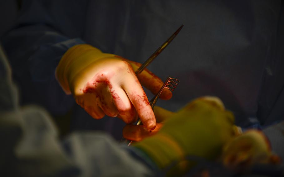Capt. James Bates repairs a broken arm of an Afghan soldier injured in a rocket-propelled grenade attack on Sept. 17, 2013.