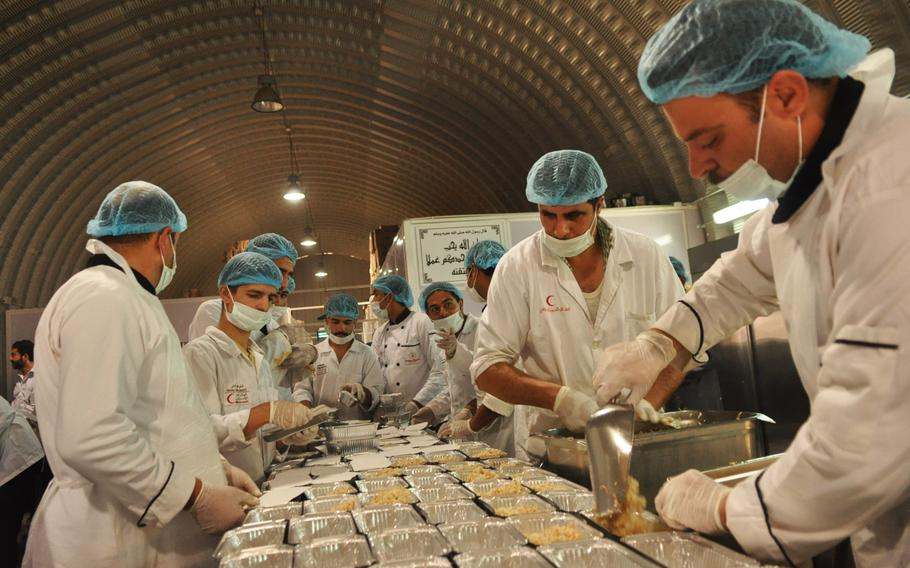 """Food is prepared for residents of a Syrian refugee camp in Jordan that is funded and run by the United Arab Emirates Red Crescent Society.  Each refugee living here receives three meals a day. Because the camp offers a higher level of service than others, it is called the 'five-star camp."""""""
