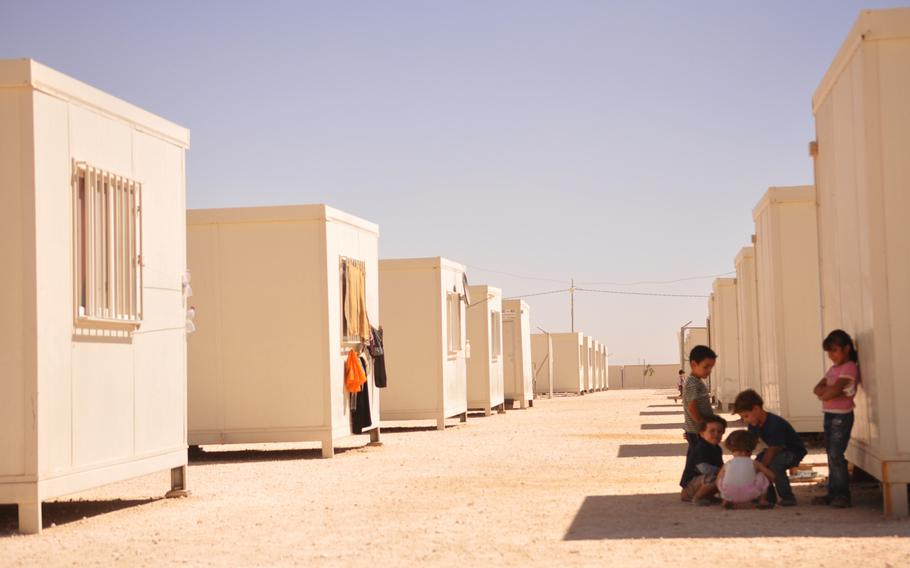 Children sit outside of their trailers at a camp for Syrian refugees in Jordan that is funded and run by the United Arab Emirates Red Crescent Society.