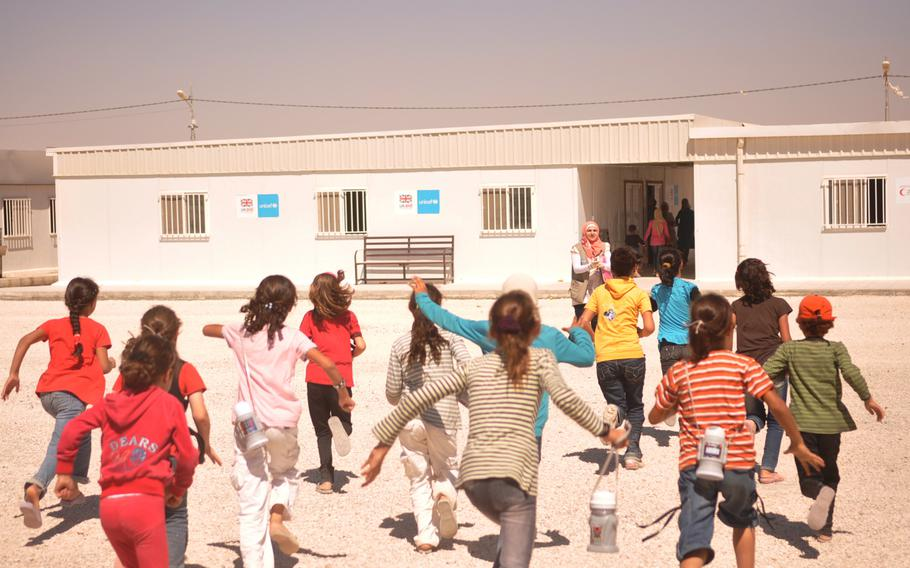 Girls run toward their teacher and school at a camp for Syrian refugees in Jordan that is funded and run by the United Arab Emirates Red Crescent Society. Children of all ages are expected to attend school while living at the camp.