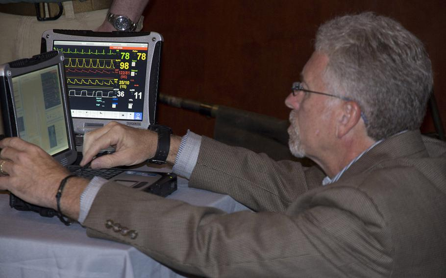 Kit Lavell, executive vice president of San Diego-based Strategic Operations, Inc., monitors the two computers hooked up to the simulator dummy that tells him how the body is doing and responding to the people training on him. On Tuesday, the newest generation of combat trauma training devices were displayed on Capitol Hill.