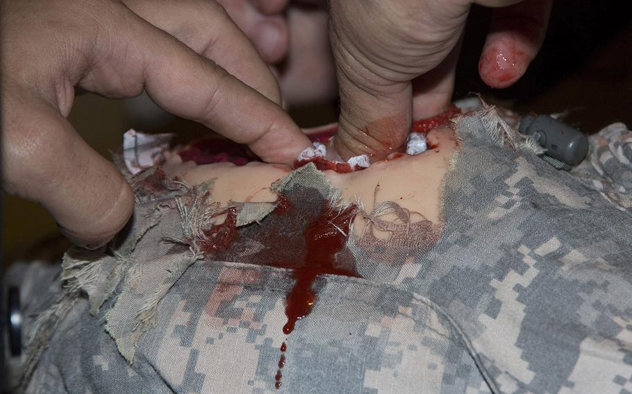 Fake blood comes from a wound on a simulator leg at a Capitol Hill demonstration Tuesday of new combat trauma training devices.