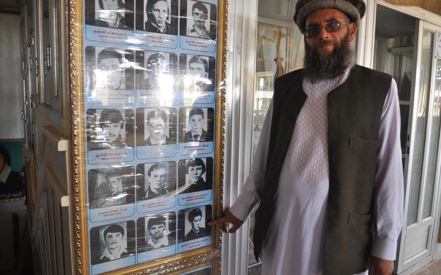 Sheikh Abdullah points at a photo of himself as a young Soviet soldier in Afghanistan, when he went by his birth name, Bakhretdin Khakimov, at Herat, Afghanistan's Jihad Museum.