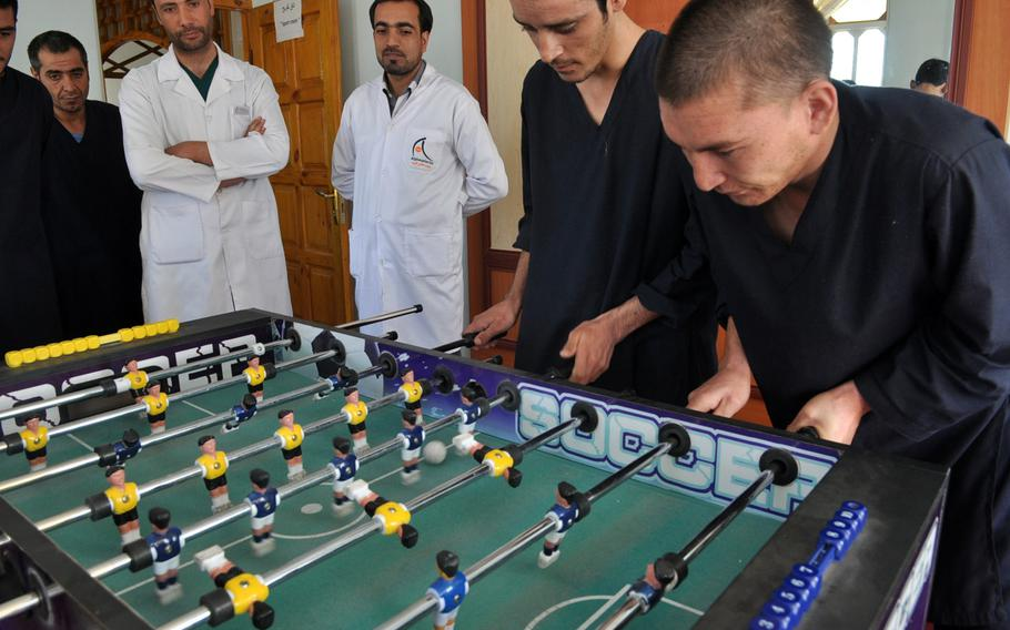 Patients play foosball while under the watch of doctors at a drug rehabilitation clinic in Herat, a city in western Afghanistan. The 45-day in-patient program includes heavy doses of motivational speaking and religion, but addicts must quit cold turkey, as no methadone is allowed.