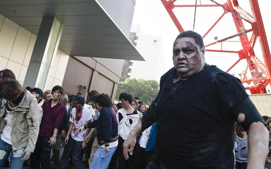 Akebono, former sumo grand champion, takes part in the storming of Toyko Tower on Oct. 31, 2013, during an event marking the start of the fourth season of the television show ''The Walking Dead.''