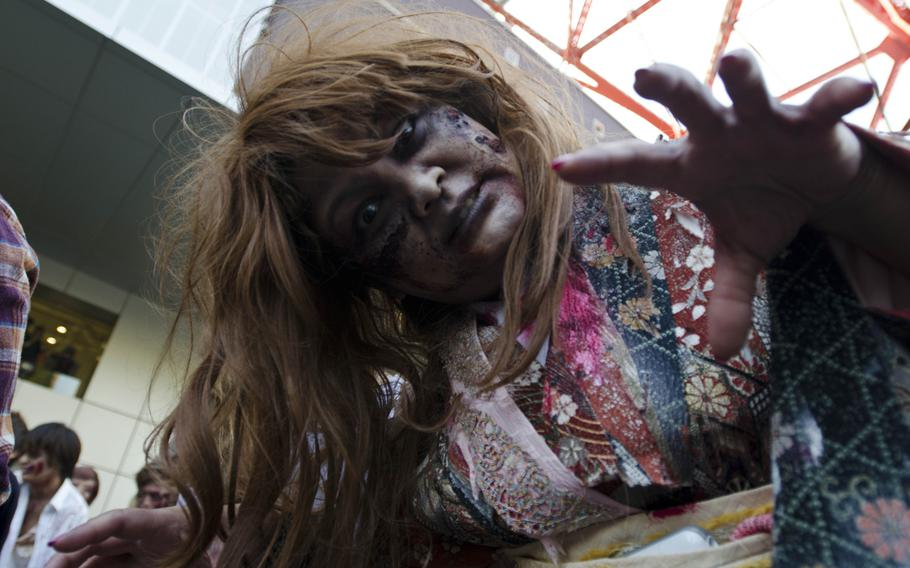 Zombies storm Toyko Tower in Tokyo on Halloween as part of an event organized by Fox International Channels, Japan, to mark the beginning of the fourth season of ''The Walking Dead'' television show.