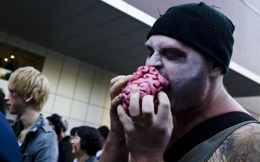 A zombies enjoys a light snack during the storming of Toyko Tower, as part of an event organized by Fox International Channels, Japan, to mark the beginning of the fourth season of ''The Walking Dead'' television show.