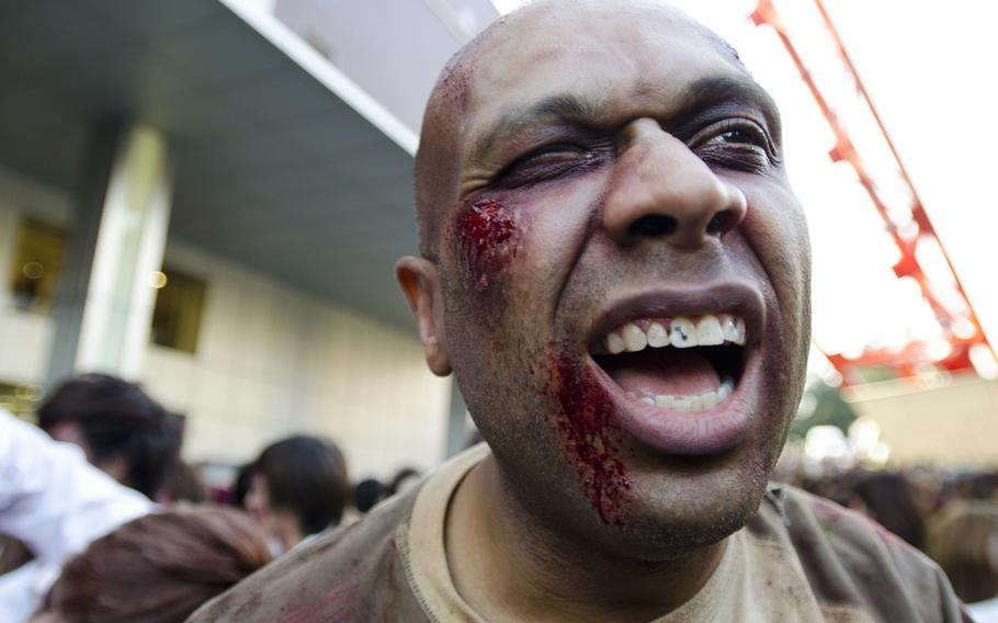 A zombie looks for a fresh victim as the undead stormed Tokyo Tower as part of an event marking the beginning of the fourth season of ''The Walking Dead'' television show.