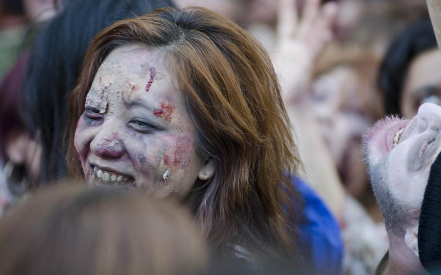 A Japanese woman dressed as a zombie laughs during the storming of Tokyo Tower on Halloween.