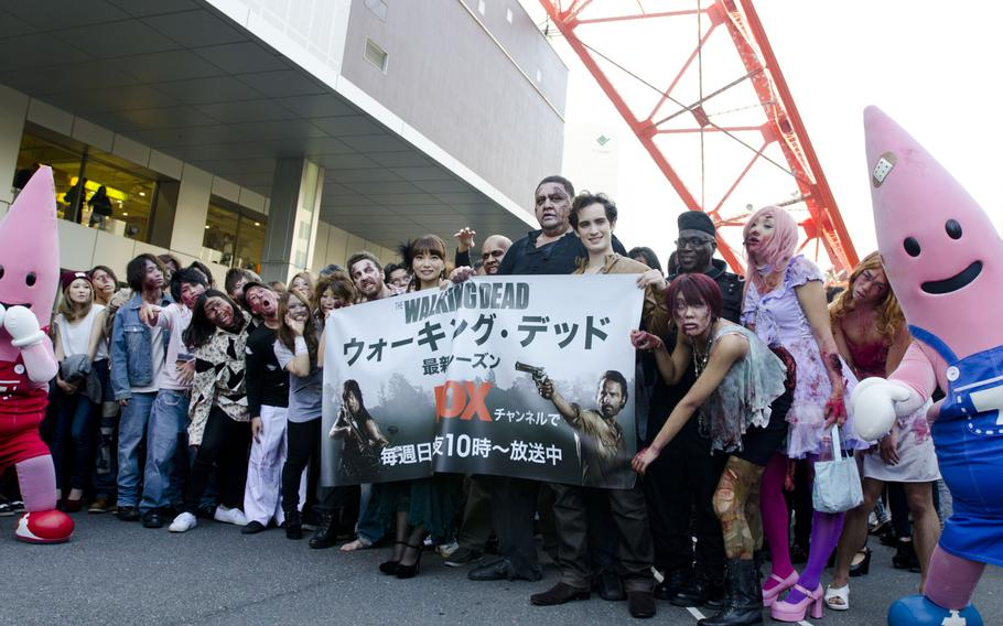 A throng of zombies, including former sumo champion Akebono, pose for a photographer during the storming of Tokyo Tower on Halloween. The event was Fox International Channels, Japan, to mark the beginning of the fourth season of ''The Walking Dead'' television show.
