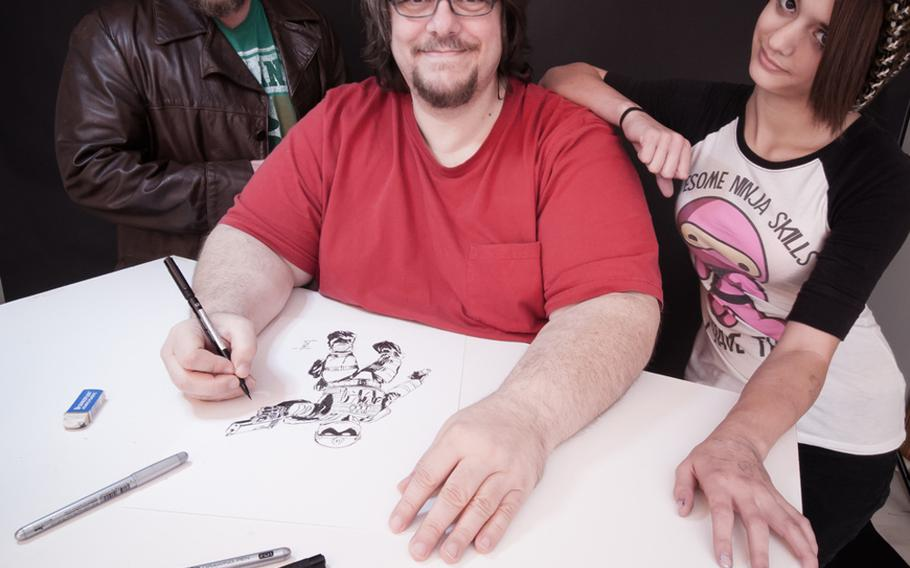 Illustrator Gerry Kissell, center, draws a frame from the soon-to-be-released graphic novel Vindicated Inc. in October at his Springfield, Mo. studios. Kissell is surrounded by his daughter Zoe, right, and co-writer Robert Scott McCall, left, who helped develop the characters and story.