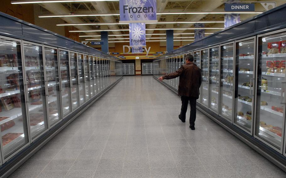 The renovated Ramstein Commissary has an expanded frozen foods section and wider aisles, among other features. Harry Nichols, the store's director, shows off the space where shelves are already stacked with frozen pizza and other items.
