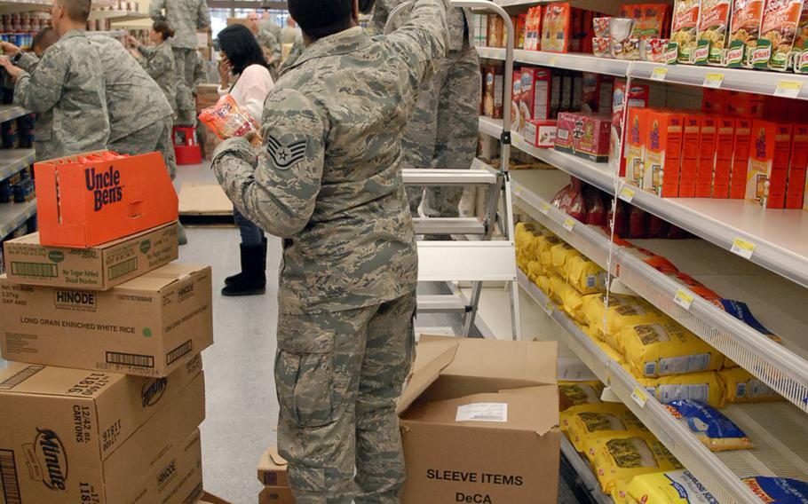 Air Force Staff Sgt. Raymond Hart, left, hands boxes of rice to Air Force Master Sgt. Johnnie Grove inside the newly remodeled Ramstein commissary. Hart and Grove were among 27 airmen from the Deployment Transition Center at Ramstein who volunteered to help stack shelves inside the remodeled store Tuesday. The store is scheduled to open Nov. 15.