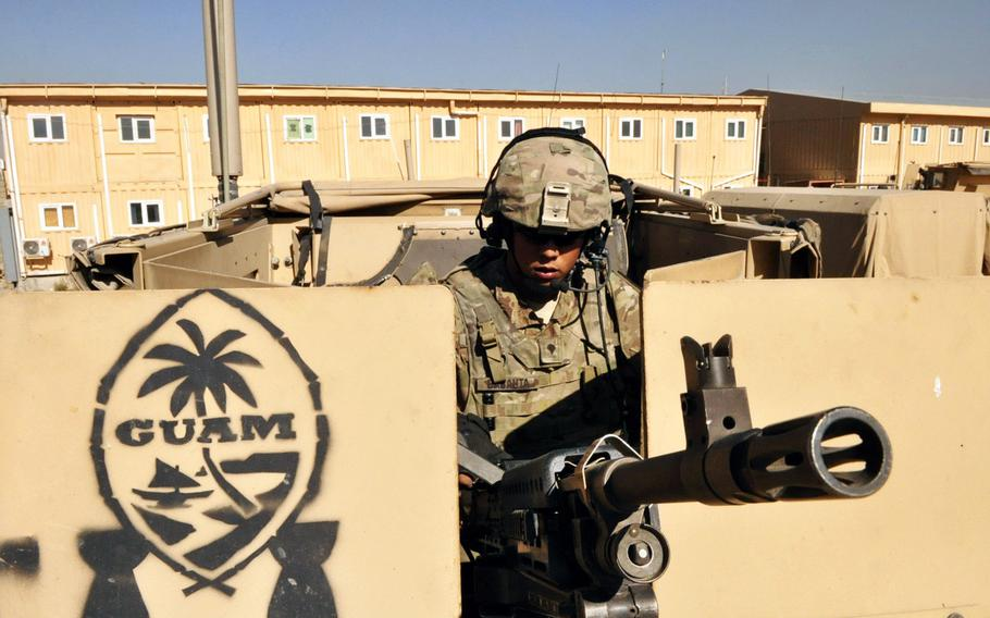 Spc. Joshua Babauta, a gunner with Headquarters Company, 1st Battalion, 294th Infantry Regiment, loads his gun atop a MRAP in preparation for a security escort mission in Kabul. The logo painted on the gun's side shield is in the shape of a sling stone, representing the warrior culture of Guam's Chamorro people.