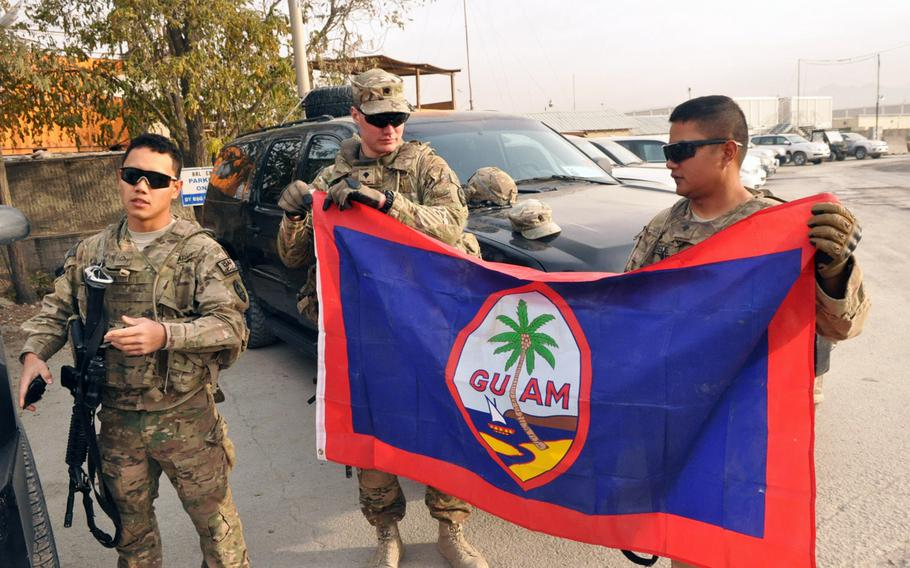 Pvt. 1st Class Raymond A.L. Dulla, left, and Spc. Thomas Clark, center, hold  the flag of Guam before a guardian angel mission in Kabul.