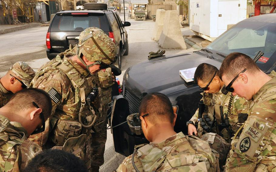 Soldiers from the 1st Battalion, 294th Infantry Regiment, Guam Army National Guard bow their heads and pray before a security escort and guardian angel mission in Kabul. The Task Force includes a group of soldiers who sing at the Catholic mass every Sunday at Camp Phoenix in Kabul.