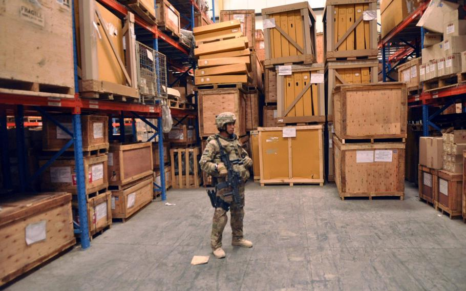 Convoy commander Sgt. 1st Class Christopher D.L. Perez, who is with Task Force Guam's 1st Battalion, 294th Infantry Regiment, stands on guard inside an Afghan National Army supply warehouse in Kabul. Perez was on a guardian angel mission to protect a lieutenant colonel while he spoke with commanders in the Afghan National Army about supplies and logistics for their troops.