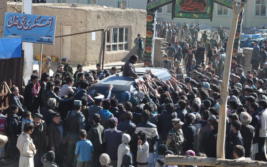 Afghans rush a van full of food to be handed out to the poor Thursday in Bamiyan, Afghanistan, in accordance with Ashura, one of the holiest days of the year for Shia Muslims.