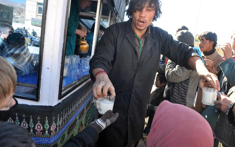 A man hands out hot, sweet milk to children Thursday after Ashura services at the central mosque in Bamiyan, Afghanistan.