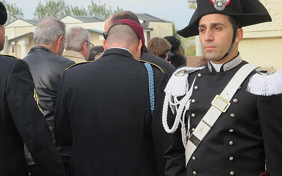 """An Italian Carabinieri stands post at the entrance to the Grantorto cemetery as Iocals and 173rd soldiers file in. They were preceded by a brass marching band which next lead the group to the town piazza to unveil a new monument to 1st Sgt. Michael Curry and Carabiniere Denis Frison. Both were """"Caduti Per La Pace"""" - fallen in the cause of peace, according to the monument's inscription."""