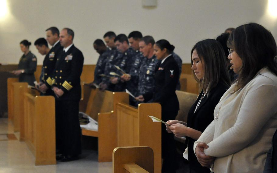 Jennifer Cruz, holding the program in the foreground, participates in a Nov. 12, 2013, ceremony commemorating the 1988 bombing of the city's USO club, which killed her sister, Petty Officer 3rd Class Angela Santos, and four Italians. Maurizio Garzelli, a USO accountant and survivor of the attack, also spoke during the program.