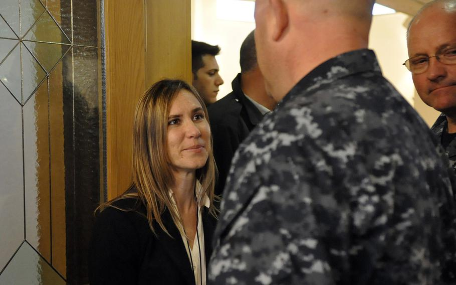 Jennifer Cruz greets Navy personnel in Naples, Italy, following a Nov. 12, 2013, ceremony commemorating the 1988 bombing of the city's former USO club. Cruz's sister, Petty Officer 3rd Class Angela Santos, was one of five people killed in the blast.
