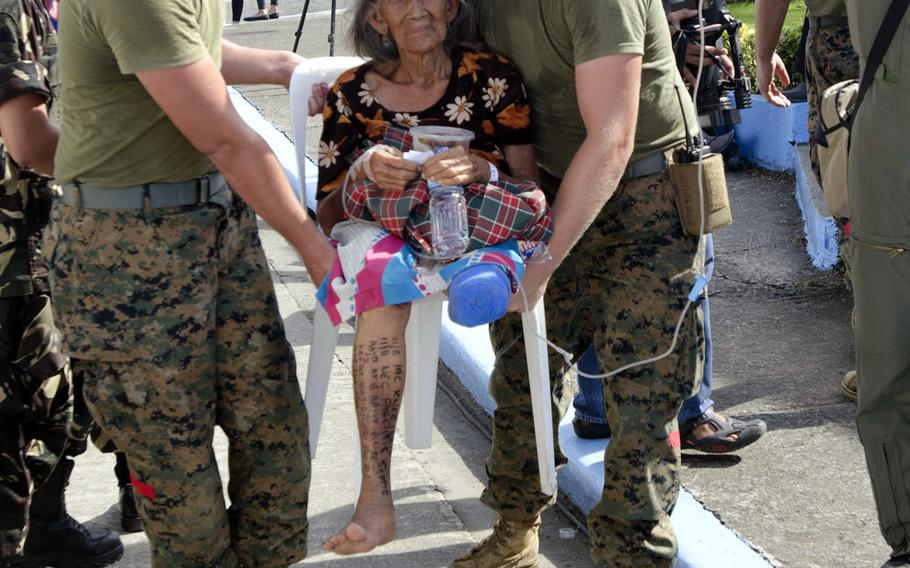 Two U.S. Marines assist a typhoon victim with a freshly amputated leg to safety at Villamor Airbase in Manila, Philippines, November 15, 2013.