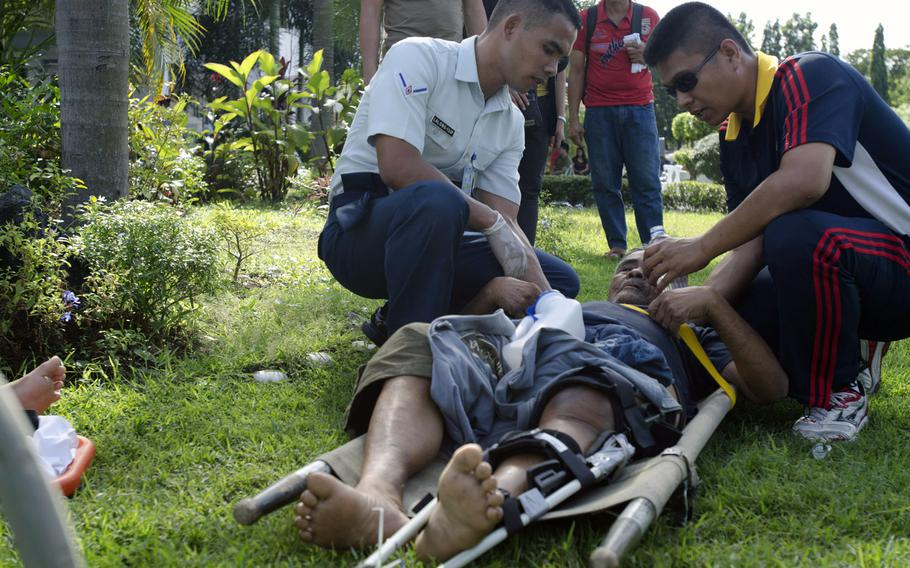 Rescue workers give water to a typhoon victim with a broken leg at Villamor Airbase, Manila, Philippines, November 15, 2013.