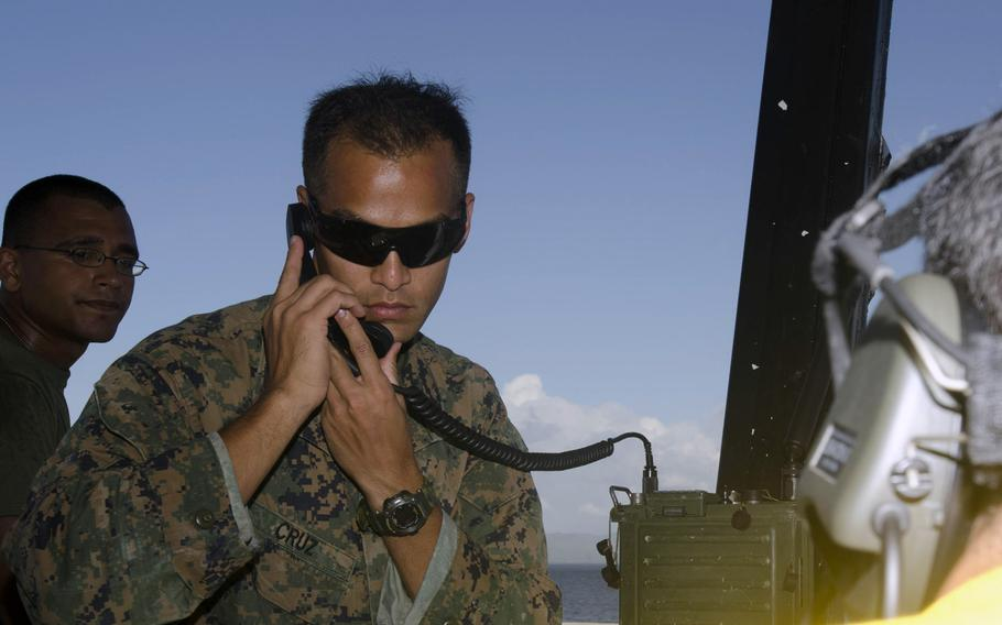 U.S. Marine Gunnery Sgt. Louie Cruz communicates with air assets at Tacloban Airport on November 16, 2013, as they coordinate flights in and out of Tacloban to Manila, Philippines.
