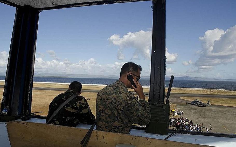 U.S. Marine Gunnery Sgt. Louie Cruz, right, communicates with air assets at Tacloban Airport on November 16, 2013, as troops coordinate flights in and out of Tacloban to Manila, Philippines.