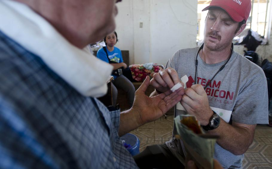 Breaux Burns, a paramedic and former active duty Marine, tests a patient's blood sugar levels at a field hospital in Tacloban, Philippines, Nov. 15, 2013.  Eric Guzman/Stars and Stripes
