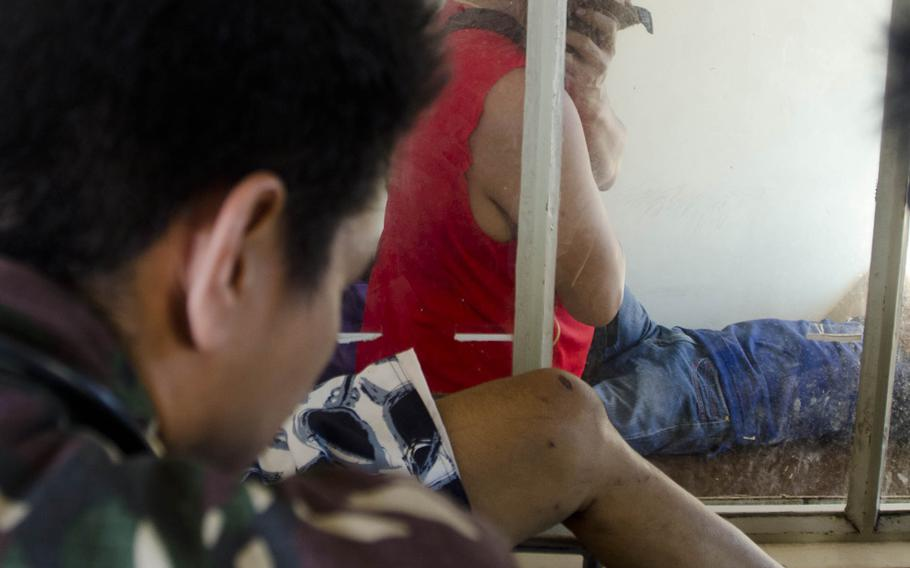 A patient at a field hospital in Tacloban, Philippines, looks on as doctors assess the injuries of another patient on Nov. 15, 2013.  Eric Guzman/Stars and Stripes