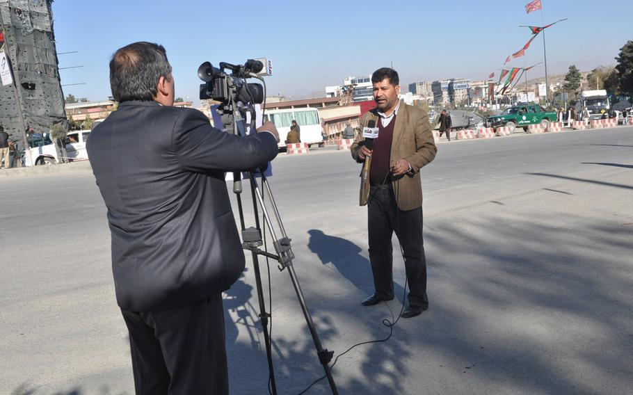 A TV reporter sets up a live shot on a road leading the building hosting the Loya Jirga, a council of elders and local leaders from around the country, which begins Wednesday. The council will be considering a proposed U.S.-Afghan security accord that is a pre-condition for the U.S. to keep troops in the country beyond 2014.  Heath Druzin/Stars and Stripes