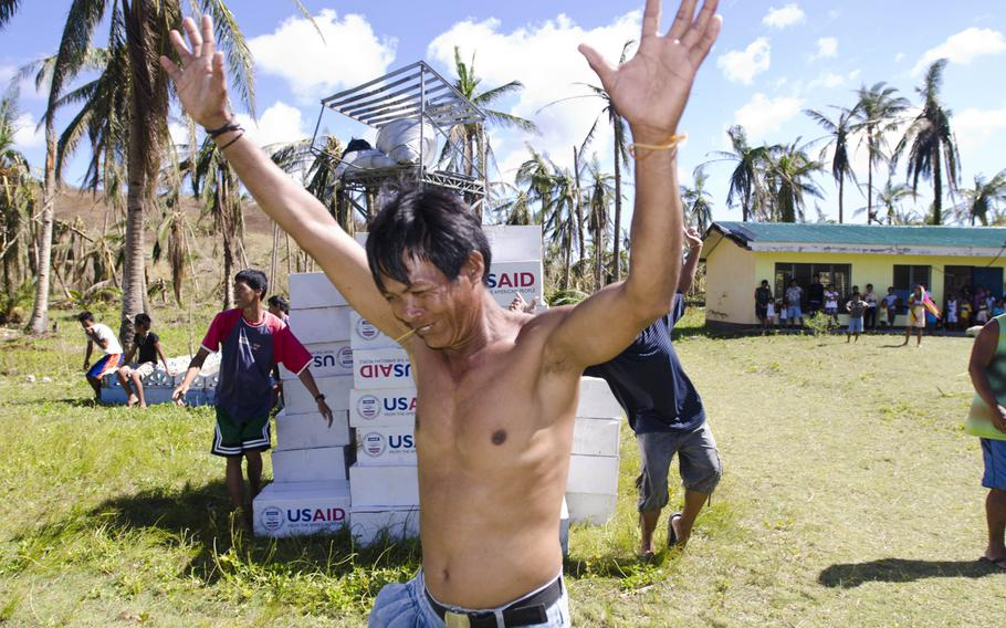 A victim of Super Typhoon Haiyan celebrates as relief packages from USAid are delivered by a V-22 Osprey crew Nov. 18, 2013.