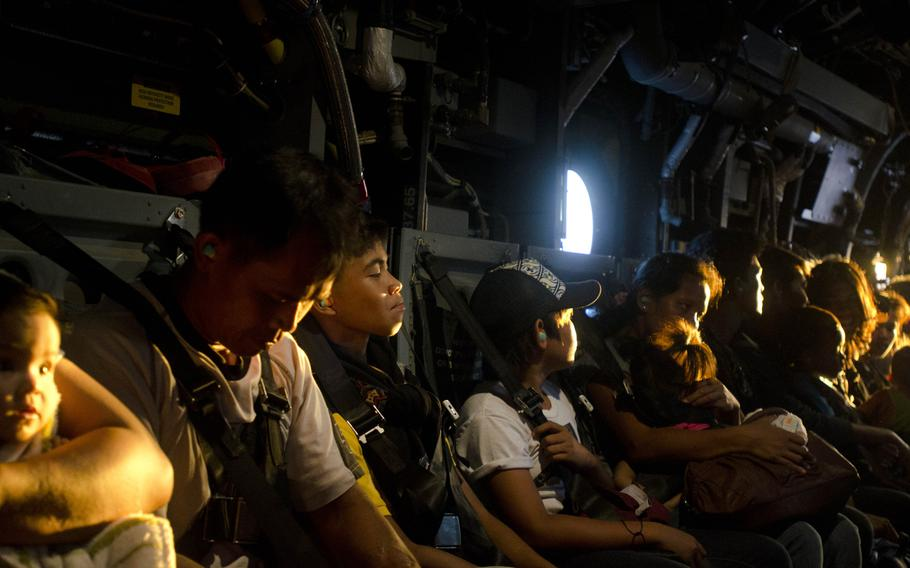 Victims of Super Typhoon Haiyan wait for a V-22 Osprey to lift off and deliver them to an evacuation center located at Manila, Philippines, Nov. 18, 2013.