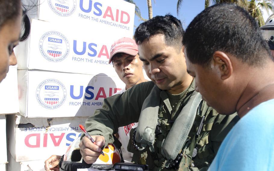 Capt. Adrian Evangelista, pilot, and Allan Naputo, village chairman, speak after boxes of relief supplies were dropped off near Calasi, Philippines, Nov. 18, 2013.