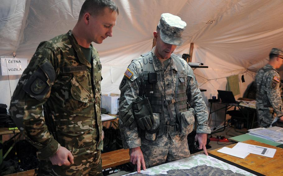 Brig. Gen. Walter Piatt, head of the Joint Multinational Training Command, talks with Slovenian 1st Lt. Savinsek Primoz about tactics on Nov. 13, 2013, during war games at the Army's training center in Hohenfels, Germany. U.S. and European militaries are working together as a multinational combat brigade. The exercise is intended to boost the combat effectiveness of a joint combat unit.