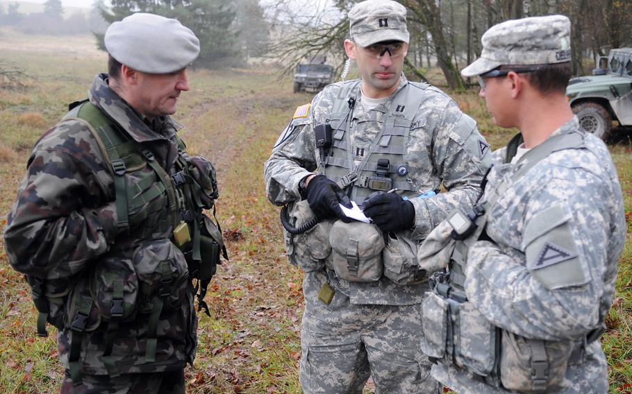 Capt. Brice Roberts, an observer controller at the Joint Multinational Readiness Center in Hohenfels, Germany, consults with Slovenian Maj. Dragomir Cevriz and Army Sgt. 1st Class Levine Delprado on Nov. 14, 2013, during Combined Resolve, which aims to bolster the interoperability of U.S. and European troops. Roberts, center, and his partners are reviewing the performance of a Slovenian mortar company.