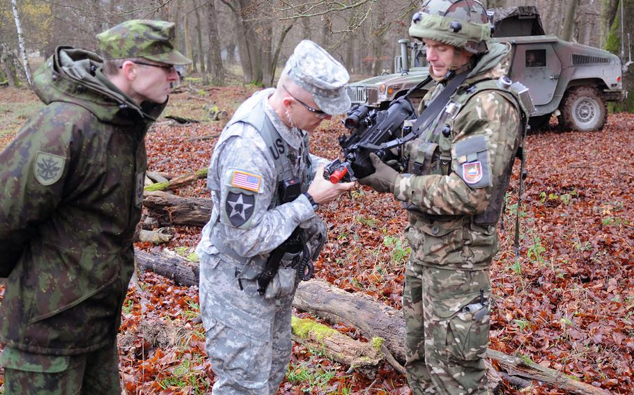 Col. John Norris, commander of the Multinational Readiness Center in Hohenfels, Germany, inspects the weapon of a Slovenian soldier on Nov. 14, 2013, during the exercise Combined Endeavor. One challenge for troops is getting U.S. scopes to work together with European systems.