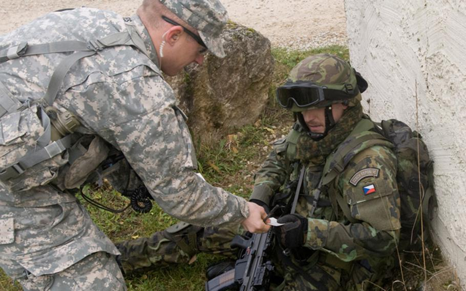 A U.S. observer/controller hands a casualty feeder card to a Czech soldier  during an urban warfare exercise on Nov. 11, 2013, at at the Hohenfels Training area, Germany. Casualty feeder cards show any simulated injuries a soldier has sustained to allow his fellow soldiers training in giving first aid.