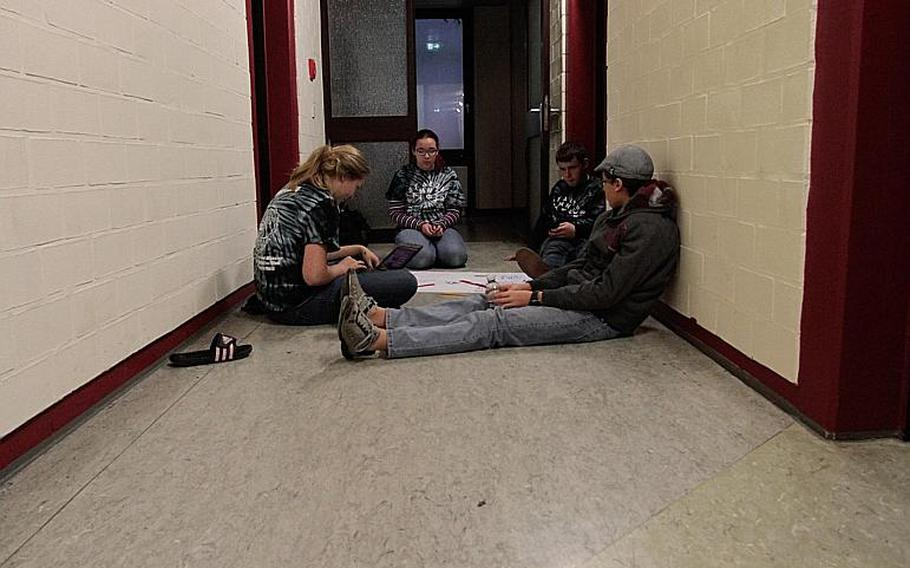 Students assigned to the civil and structural engineering team of the DODDS-Europe STEMposium brainstorm in the hallway.