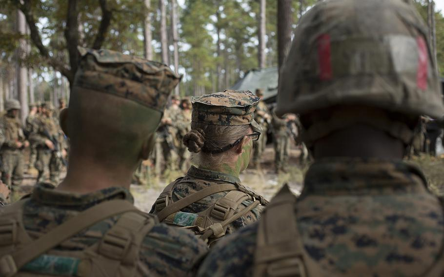 U.S. Marines listen to a combat order brief Nov. 15 before stepping off on a raid, which is part of the Infantry Integrated Field Training Exercise at Camp Geiger, N.C.  This is the first company with female students. The Marine Corps is collecting data on the performance of female Marines when executing existing infantry tasks and training events for possible placement in jobs currently limited to males.