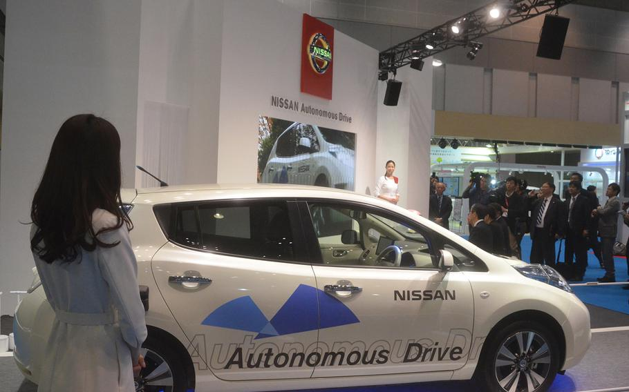 Nissan officials discuss their driverless concept car at the 2013 Tokyo Motor Show.